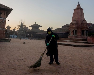 A worker wearing the protective dress cleaning the Bhaktapur Durbar Square area